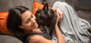 Woman cuddling dog on couch at Brix Apartments