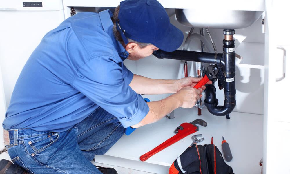 Man fixing plumbing underneath sink