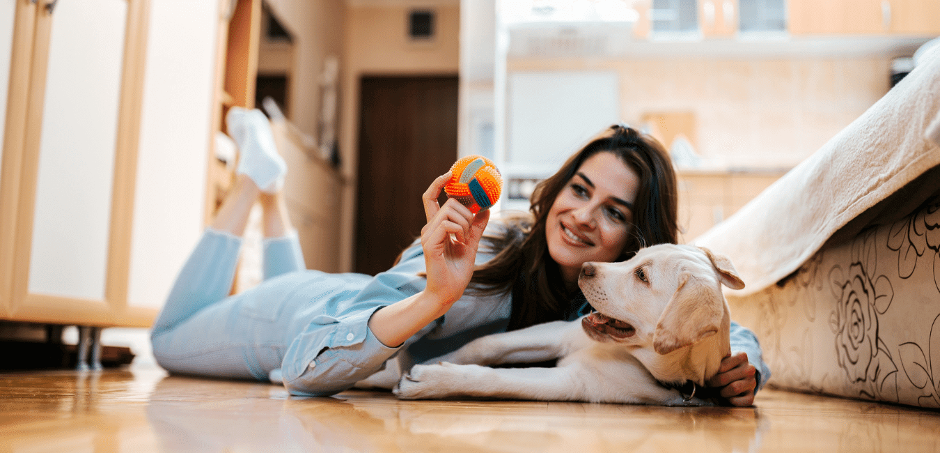 Woman playing with dog on floor at apartment