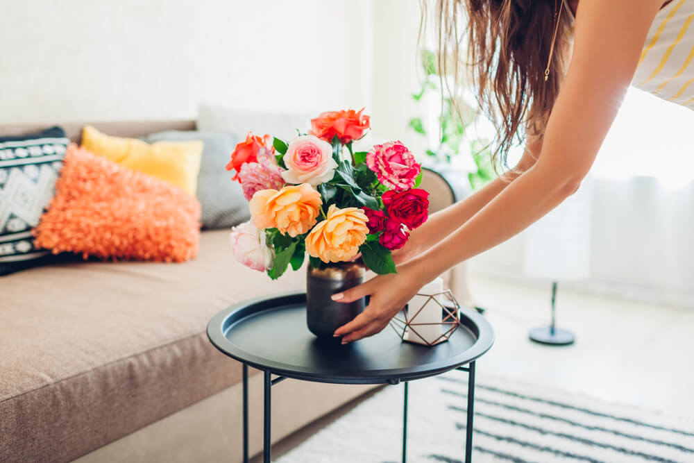 Woman putting flower pot on small coffee table
